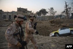 Croatian soldiers from the NATO coalition walk past a crater from a bomb blast as they inspect the site of an attack targeting the German Consulate in Mazar-e Sharif on November 11.