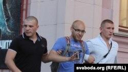 Қарапайым киінген қауіпсіздік қызметкерлері наразылық шарасына қатысқан адамды қамауға алып келе жатыр.Mинск. 20 шілде 2011 жыл.