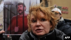 Alla Bout, the wife of jailed Russian arms dealer Viktor Bout, stands in front of a photo of Bout in jail.