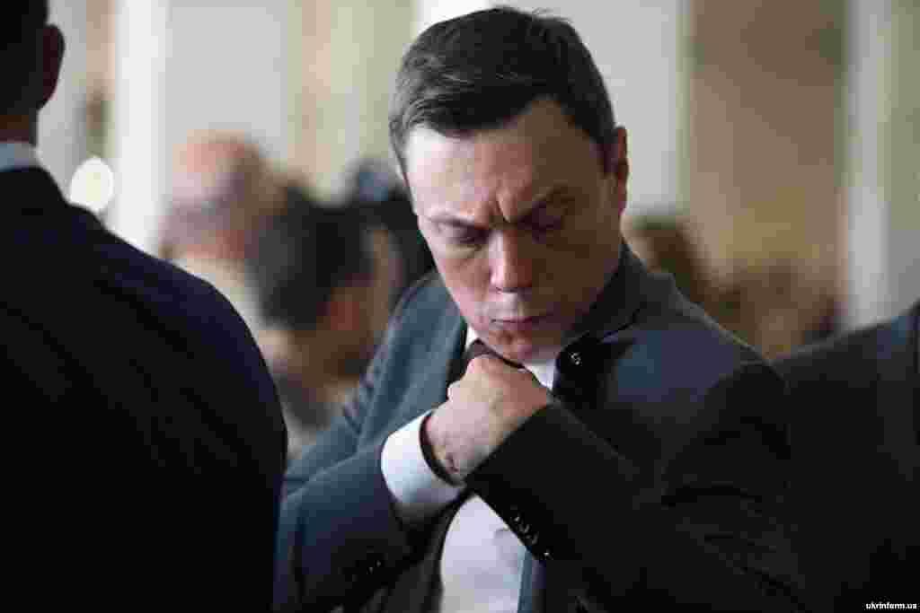 Новообраний народний депутат України прикручує до піджака депутатський значок