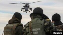 Українські прикордонники спостерігають як російський гелікоптер Мі-35 пролітає поряд з кордоном України з Росією, Херсонська область, 16 березня 2014 року