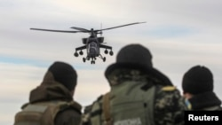 A Russian army chopper patrols the area as Ukrainian servicemen guard a checkpoint near the village of Strelkovo in the Kherson region adjacent to Crimea. Ironically many of the engines used by Russia's military helicopters are made in Ukraine.