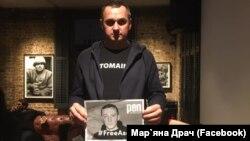 Олег Сенцов тримає плакат #FreeAseyev
