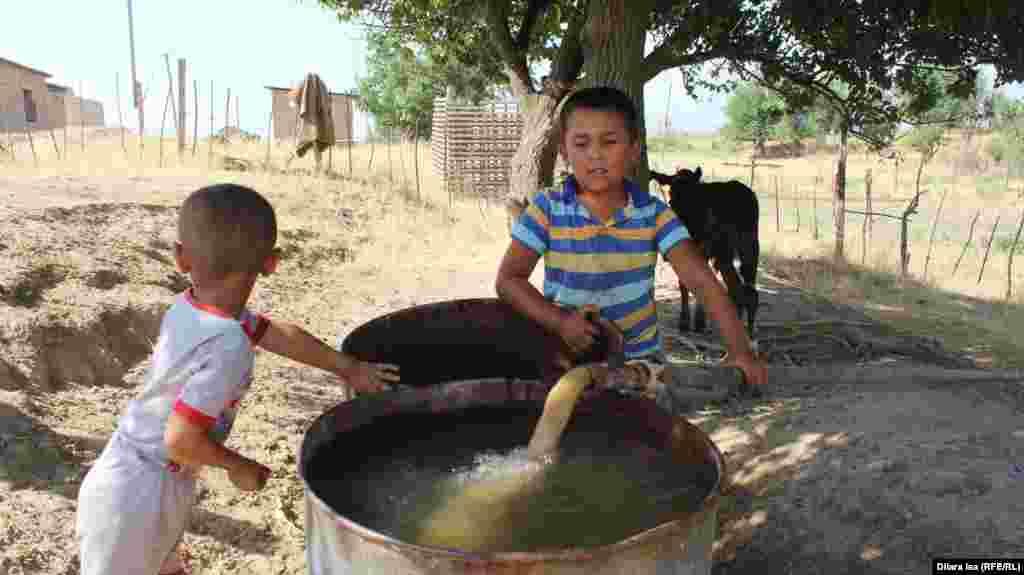 Балалар Достық ауылы тұрғындарына әкімдік қазып берген құдықтан бөшкелерге су толтырып, тұндырып, күнге жылытып, шомылады.