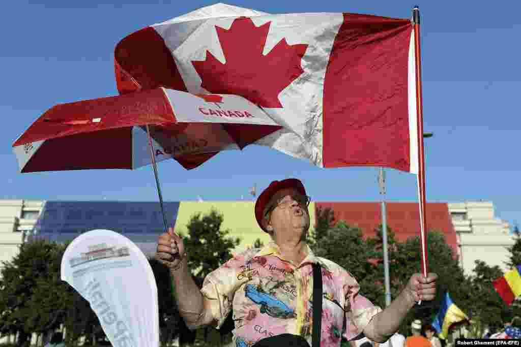"A protester waves a Canadian flag on August 12, as a third night of protests began. The protests have been dubbed the ""diaspora protests"" due to the number of Romanians who traveled home from abroad to take part in the demonstrations."
