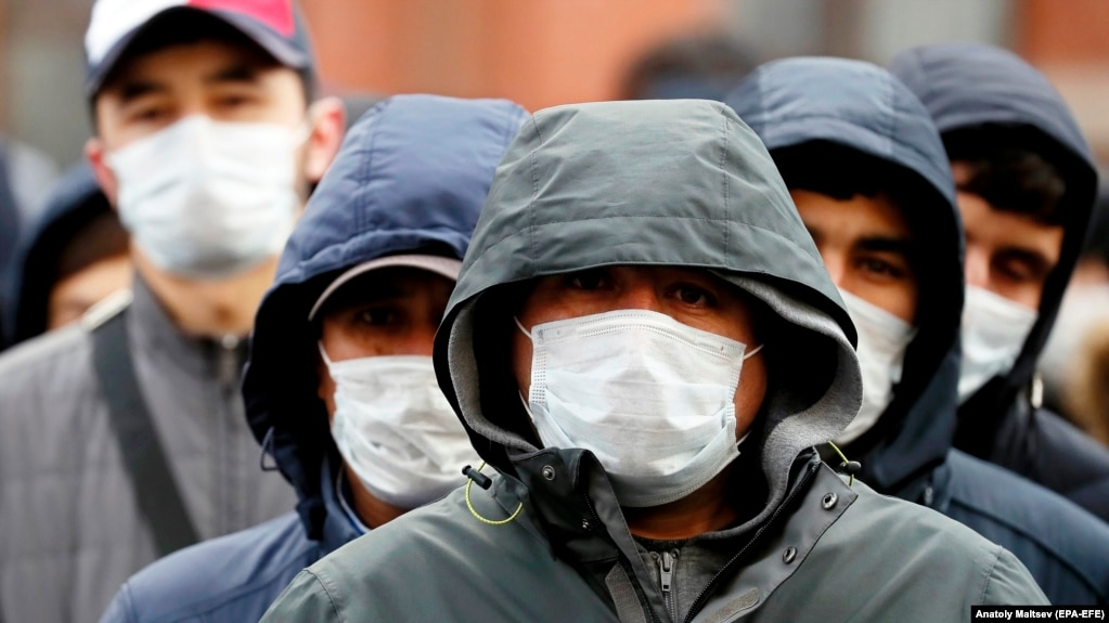 Migrant workers wearing protective face masks line up outside a migration control center to prolong their stay in Russia amid the ongoing coronavirus pandemic in St. Petersburg on April 3.