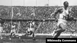 Джеси Оуенс печели олимпийски медал пред погледа на Адолф Хитлер в Берлин