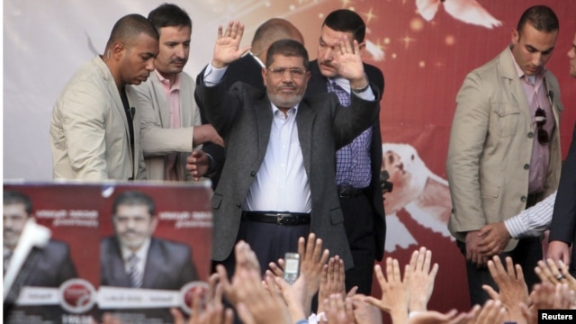 Egyptian President Muhammad Morsi (center) waves after speaking to supporters in front of the presidential palace in Cairo on November 23.