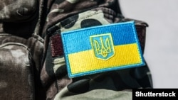 Ukraine -- ©Shutterstock military badge of ukrainian army with trident and yellow-blue flag
