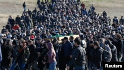Crimean Tatars gather for the funeral of Reshat Ametov -- whose naked, bound, and apparently tortured body was discovered outside Simferopol -- on March 18.