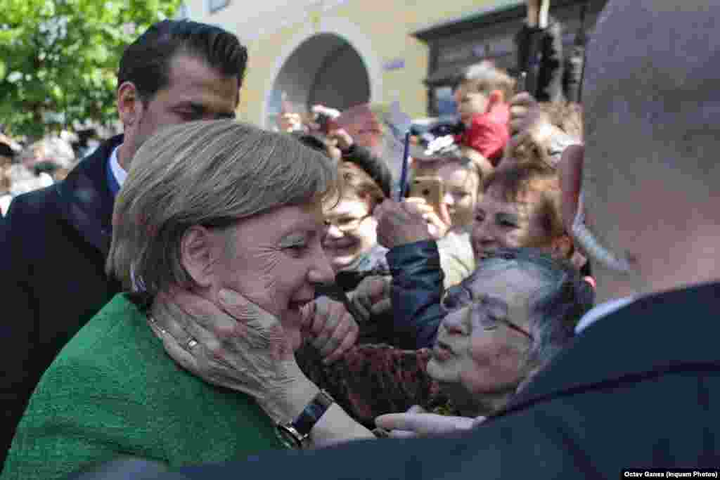 """German Chancellor Angela Merkel received a warm welcome at an EU summit in Sibiu, Romania, on May 9. In this photo, an elderly lady hugs Merkel, telling her, """"Frau Merkel, take care of my daughter,"""" who works in Germany. (Inquam Photos/Octav Ganea)"""