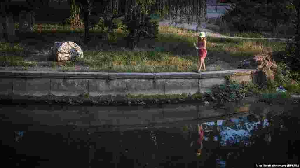 Девочка играет на набережной Салгира. Несмотря на загрязненность, на реке собирается много народа