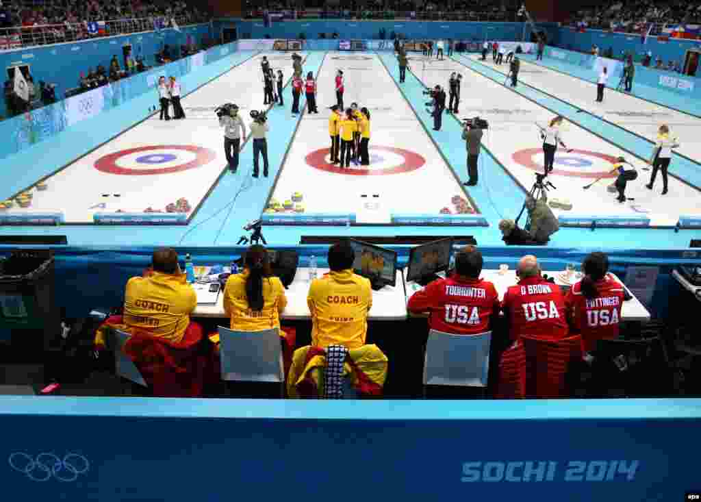 Coaches and team members of China and the United States watch their round-robin match in the curling competition in the Ice Cube Curling Center.