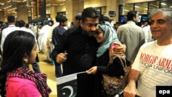 People embrace their relatives who were evacuated from Yemen, as they arrive at Jinnah International Airport in Karachi on March 30.