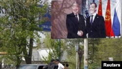 A billboard in southern Kyrgyzstan shows Russian President Dmitry Medvedev (right) with Kurmanbek Bakiev, who fled into exile after a bloody crackdown on protesters in April.