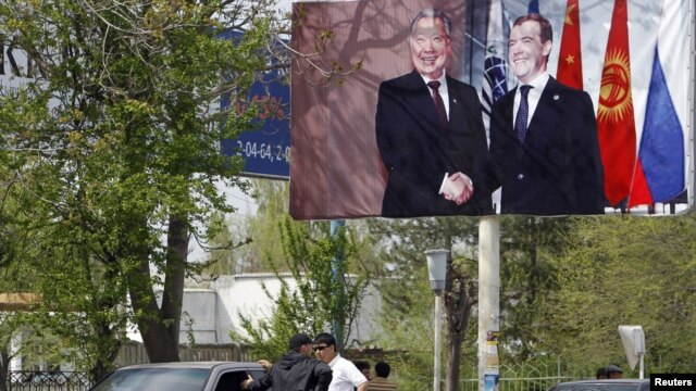 A billboard in southern Kyrgyzstan, where the ethnic violence has killed at least 170 people and injured many hundreds more, shows Russian President Dmitry Medvedev with the now-deposed Kyrgyz leader Kurmanbek Bakiev in April 2010.