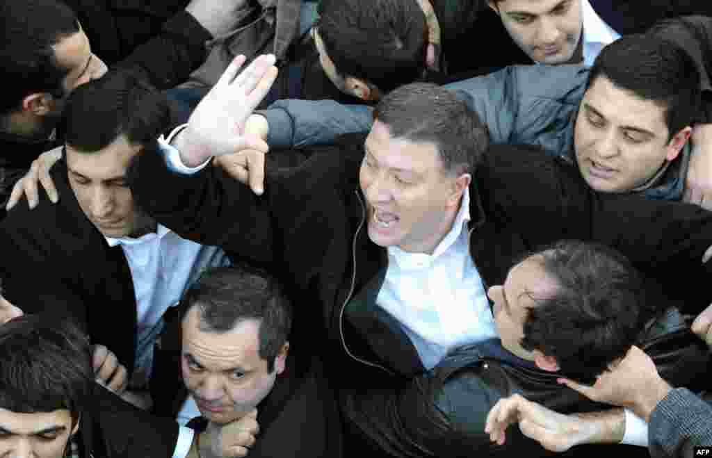 Tbilisi, 8 fevral 2013. Milli kitabxana qarşısında Saakashvili əleyhidarlarının etiraz aksiyası. Tbilsinin meri Gigi Ugulava (ortada) qəzəbli kütlənin ortasında