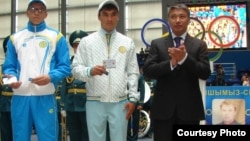 Казахстанские спортсмены (слева) и руководитель агентства спорта и физической культуры Казахстана Талгат Ермегияев во время вручения удостоверений участников Олимпиады в Лондоне. Астана, июль 2012 года.