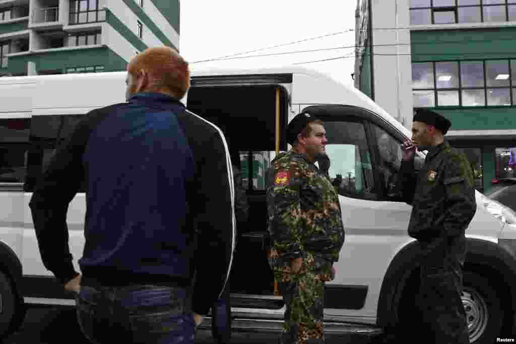 Полиция Сочи урамнарында рөхсәтсез мигрантларны аулаган арада тәмәке тарта.