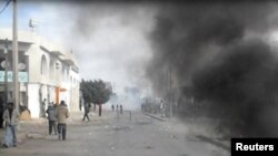 Smoke fills a street in Rgeb, Tunisia, where funeral processions were being held on January 10 for people shot in recent clashes with police.