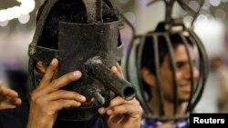 زوّار يجربون أدوات تعذيب كان يستخدمها النظام السابق في العراق، معروضة في متحف بنصب الشهيد ببغداد