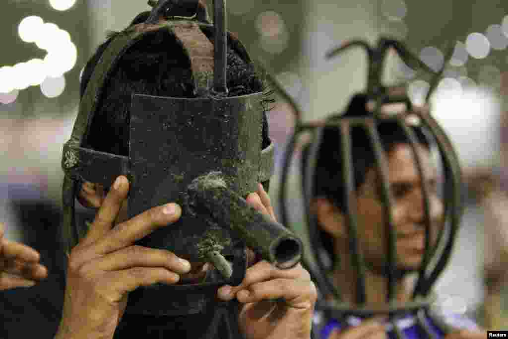 Visitors try on metal masks that were used as torture devices by the regime of Iraq's ousted leader Saddam Hussein at an exhibition at the Martyrs Monument in Baghdad. (Reuters/Thaier al-Sudani)