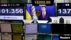 Трейдеры на фондовой бирже Токио смотрят выступление президента Украины Петра Порошенко
