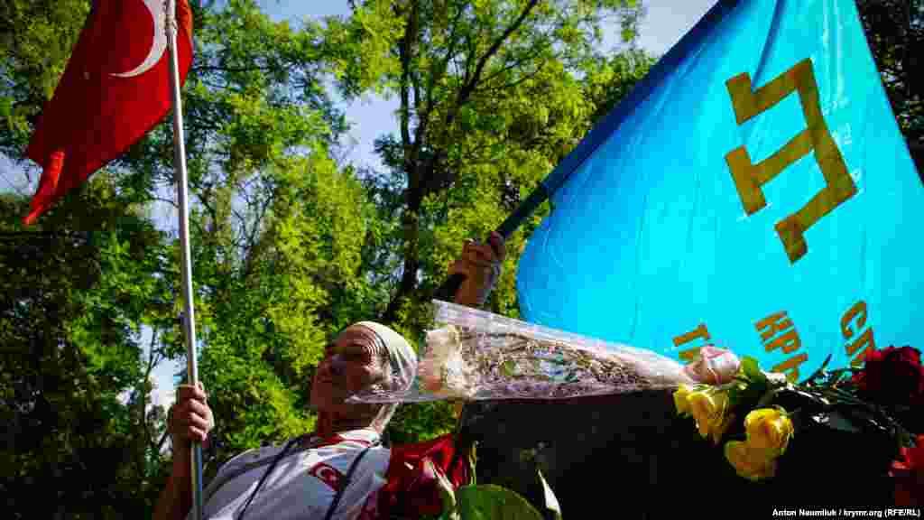На акции собралось около 100 человек с крымско-татарскими флагами, ленточками, траурными памятными нагрудными значками.