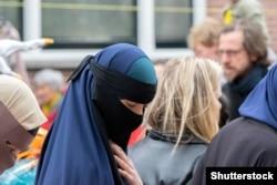 Женщина в парандже на улице Амстердама