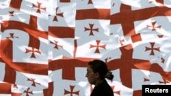 Женщина проходит мимо стены, увешанной грузинским национальным флагом. Тбилиси, 24 мая 2010 года.
