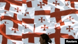 A woman walks past a wall decorated with Georgia's national flags in the center of Tbilisi.