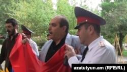 Заместитель начальника Центрального отдела полиции ведет Левона Барсегяна к полицейской машине, 21 сентября 2011 г.