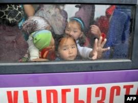Дети смотрят из окна автобуса, направлявшегося из Оша в Бишкек. 17 июня 2010 года.