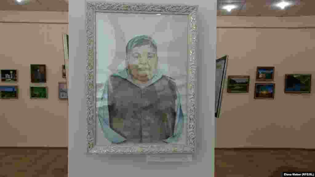 """На персональной выставке есть портрет самого Карипбека Куюкова, который написала его племянница, решившая пойти по стопам своего родственника. Куюков, который является еще и членом движения """"Невада - Семей"""", пишет картины, держа кисти и карандаши пальцами ног или зажав зубами. Это очень тяжелый труд, говорят научные сотрудники музея."""