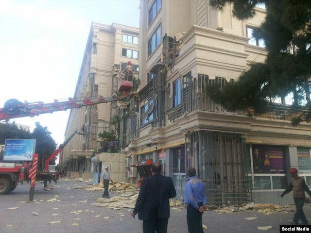 Workers remove polyurethane panels from a building in Baku.