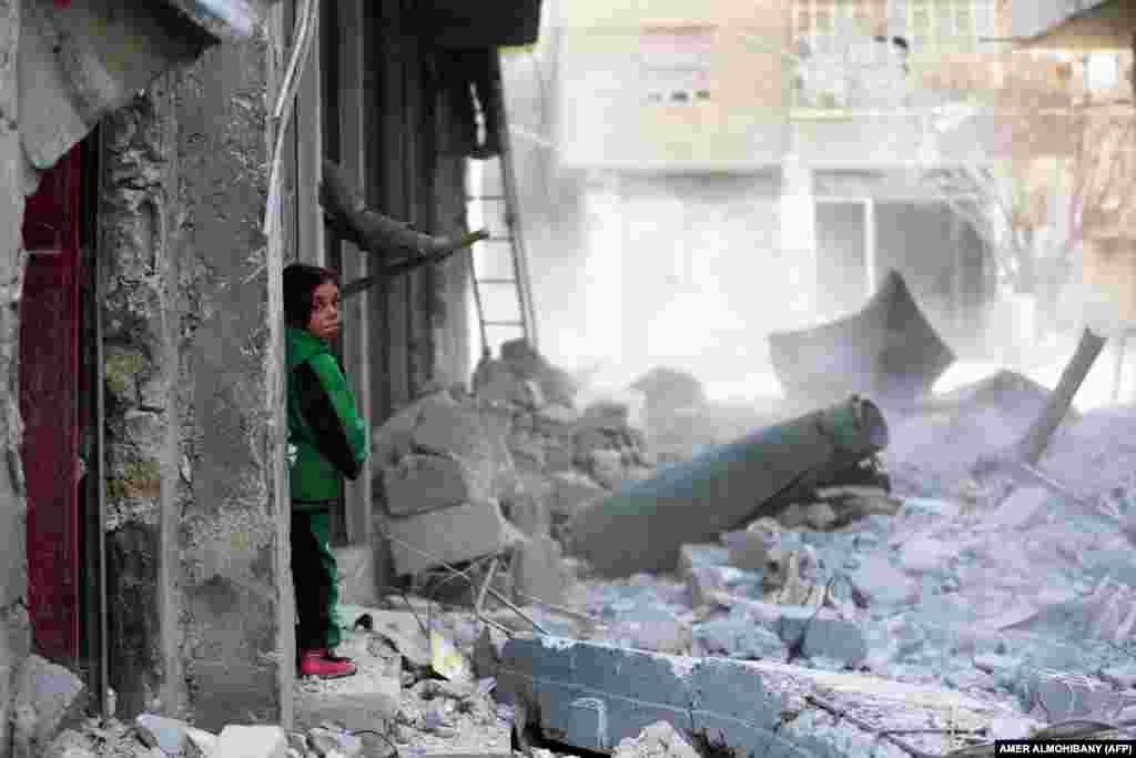 Një fëmijë në rrënojat e qytetit sirian Arbin, të mbajtur nga rebelët, rajoni i Ghoutas lindore, në periferi të Damaskut.
