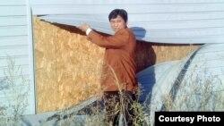 Житель поселка, построенного по программе «Нурлы кош», показывает стену из тонкого древесного материала, скрытого под сайдинговым фасадом.