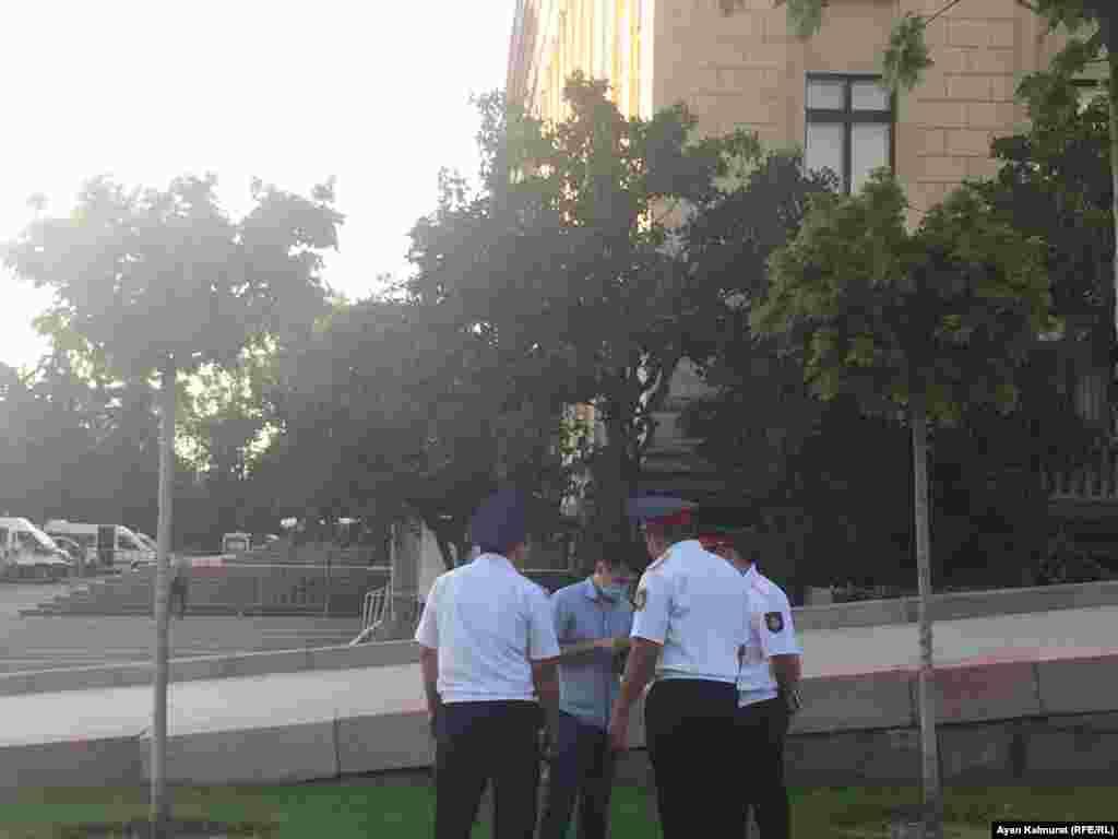 Полицейские проверяют документы у прохожего в районе площади Астана. По сообщению репортеров Азаттыка, позднее этот мужчина был уведен силовиками. Алматы, 6 июля 2018 года.