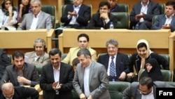 President Mahmud Ahmadinejad (left) applauds as Esfandiar Rahim Mashaei, head of his office, prepares to speak at the conference.