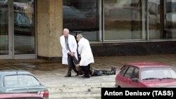 Врачи выносят погибшую женщину из здания