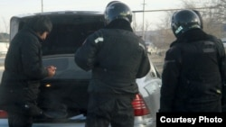 Көліктерді тоқтатып, тексеріп жатқан полицейлер. Жаңаөзен, 19 желтоқсан 2011 жыл.
