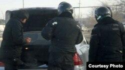 """Полицейские проводят досмотр машины. Жанаозен, 19 декабря 2011 года. Фото Елены Костюченко, """"Новая газета""""."""