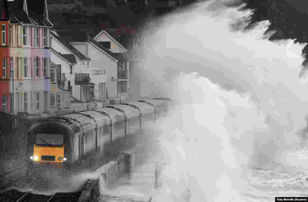 Large waves crash over a train as it passes through Dawlish in southwest Britain. (Reuters/Toby Melville)