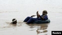 Рабочий помогает мужчине пересечь вышедшую из берегов реку близ города Файсалабад, 28 июля 2015 года.