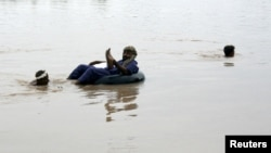 Local farm workers help a man cross the flooded Chenab River in Chinoit outside Faisalabad on July 28.