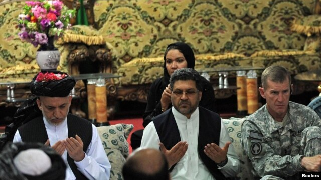 """Afghan President Hamid Karzai (left) prays at a meeting with tribal leaders in Kandahar city on June 13. """"I want your cooperation in this operation,"""" he said."""