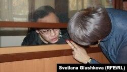 Гражданский активист Махамбет Абжан, которому предъявлено обвинение в мошенничестве, разговаривает со своим адвокатом через проем в огороженном для подсудимых помещении в зале суда. Астана, 16 октября 2017 года.