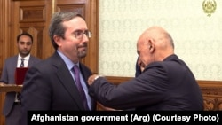 FILE: Afghan President Ashraf Ghani conferred an Afghan medal on outgoing U.S. Ambassador John Bass (L) on December 31, 2019.