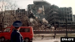 A member of a Russian delegation visiting Belgrade in April 1999 looks at the building of the Serbian Interior Ministry which was totally destroyed in overnight NATO bombing.