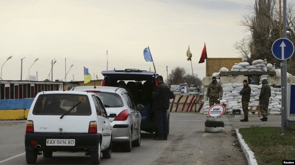 Cars lined up to pass a checkpoint, erected by ethnic Tatars and members of Ukrainian nationalist battalions, outside the settlement of Chonhar, which borders with the territory of Crimea, November 23, 2015.